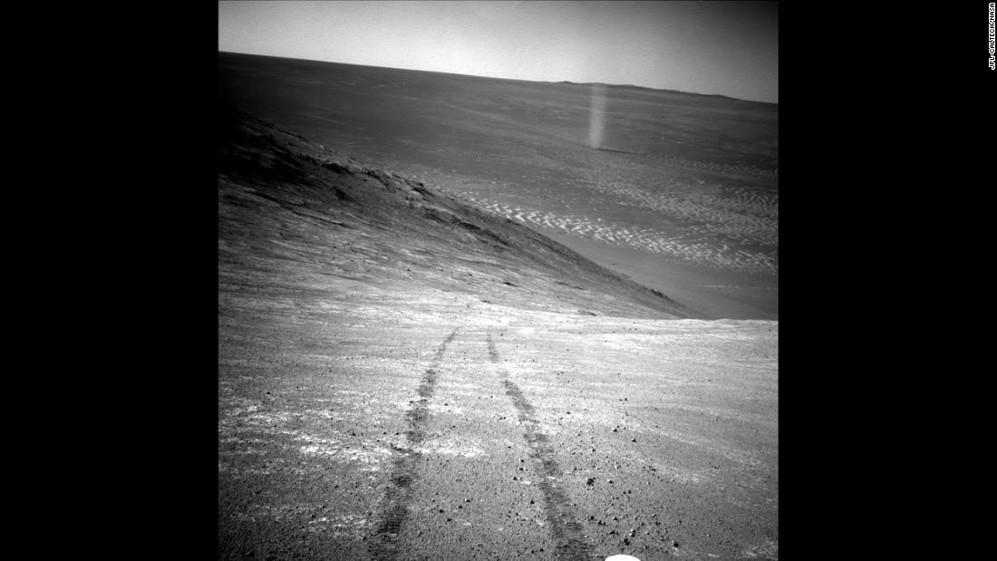 From its perch high on a ridge, Opportunity recorded this image of a Martian dust devil twisting through the valley below. The view looks back at the rover's tracks leading up the north-facing slope of Knudsen Ridge, which forms part of the southern edge of Marathon Valley.