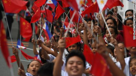 Schoolchildren wave the  flags of the Philippines and China as they line up November 20 along the route of China's President Xi Jinping's motorcade in Manila.