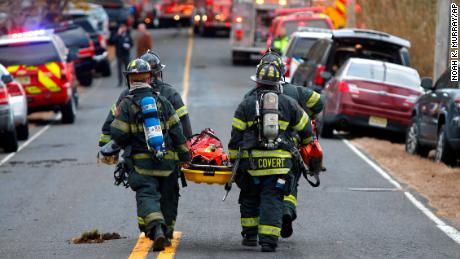 Firefighters bring a stretcher to the scene of a fatal fire on November 20, 2018 in Colts Neck, New Jersey.