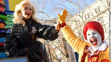 NEW YORK NY- NOVEMBER 22 Singer Rita Ora high fives with Ronald Mc Donald during the the 2018 Macy's Thanksgiving Day Parade