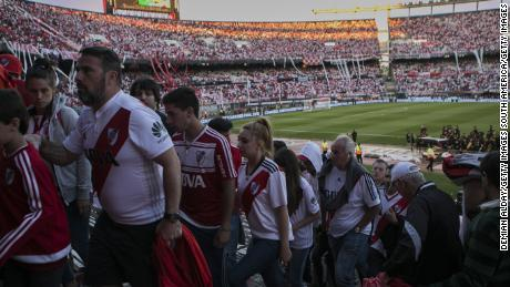 River Plate fans leave after the start of the match was postponed for a day