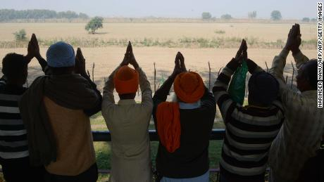 Indian Sikh devotees offers prayers as they look towards the Kartarpur temple which is situated in Pakistan from the Indian side on the outskirts of Amritsar