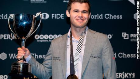 Carlsen își deține trofeul după ce l-a învins pe Fabiano Caruana pentru a-și recăpăta titlul de campion mondial de șah pe 28 noiembrie 2018 la Londra.