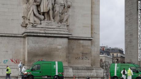 Los trabajadores limpian los grafitis del Arco de Triunfo.