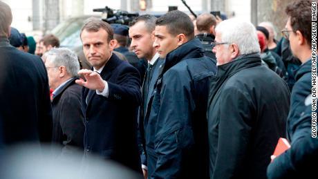 El presidente francés Emmanuel Macron saluda al salir del Café Belloy, cerca del Arco de Triunfo de París el domingo.