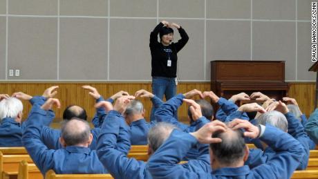 Un instructor de aeróbicos lidera a los ancianos en ejercicios simples.