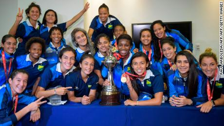 Colombia's Atletico Huila Femenino players pose with the Copa Libertadores trophy at a press conference in Bogota.