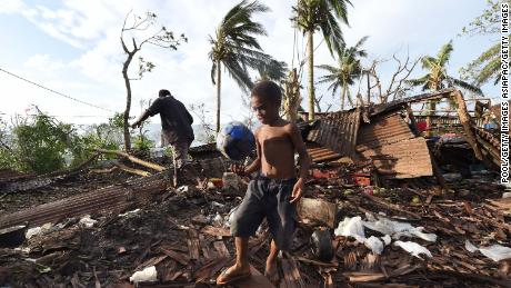 A boy walks through through the ruins of his family home with his father Phillip in 2015 in Port Vila, Vanuatu after Cyclone Pam.