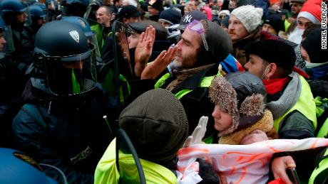 """""""Yellow vest"""" demonstrators face riot police officers Saturday in the French capital."""
