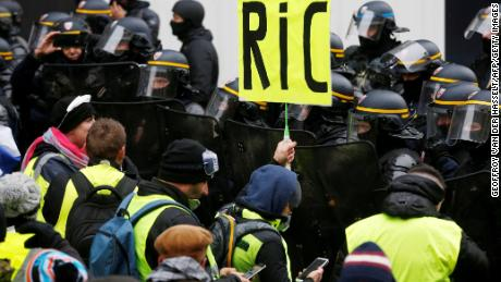 """A Paris protester holds a """"RIC"""" sign Saturday in a reference to a demand for a citizens' referendum."""