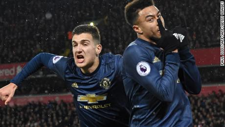 Jesse Lingard celebrates his equalizer for Manchester United at Anfield with Diogo Dalot (left).