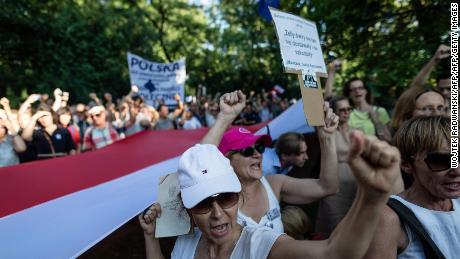 Protesters deploy a giant Polish national flag and shout slogans during a demonstration against a judicial reform pushed through by the right-wing government but criticised by the EU as a threat to judicial independence on July 24, 2018, in front of the Senate Building in the capital Warsaw.