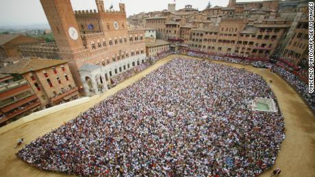 """Twice a year, riders from 10 of the city's 17 districts, known as """"contrade"""", race three times around Siena's central square to win the Palio."""