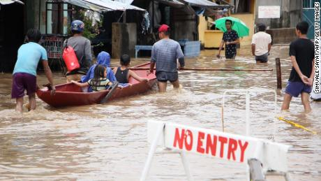 People wade through flooded streets in the town of Baao in Camarines Sur province on December 30.