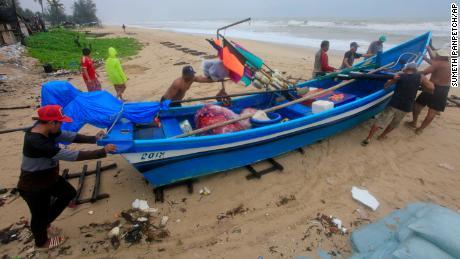 Los hombres tailandeses mueven un barco de pesca a un lugar más seguro en Songkhla, sur de Tailandia, en preparación para las condiciones climáticas de la tormenta el jueves.