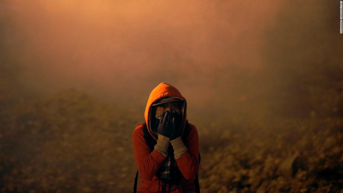"""A migrant from Central America covers his face as tear gas is fired over the US-Mexico border on Tuesday, January 1. <a href=""""https://www.cnn.com/2019/01/01/us/california-border-patrol-gas-migrants/index.html"""" target=""""_blank"""">Border agents were using tear gas, pepper spray and smoke</a> as more than 100 migrants tried to enter the United States illegally from Tijuana, Mexico. According to US Customs and Border Protection, some of the migrants were throwing rocks."""
