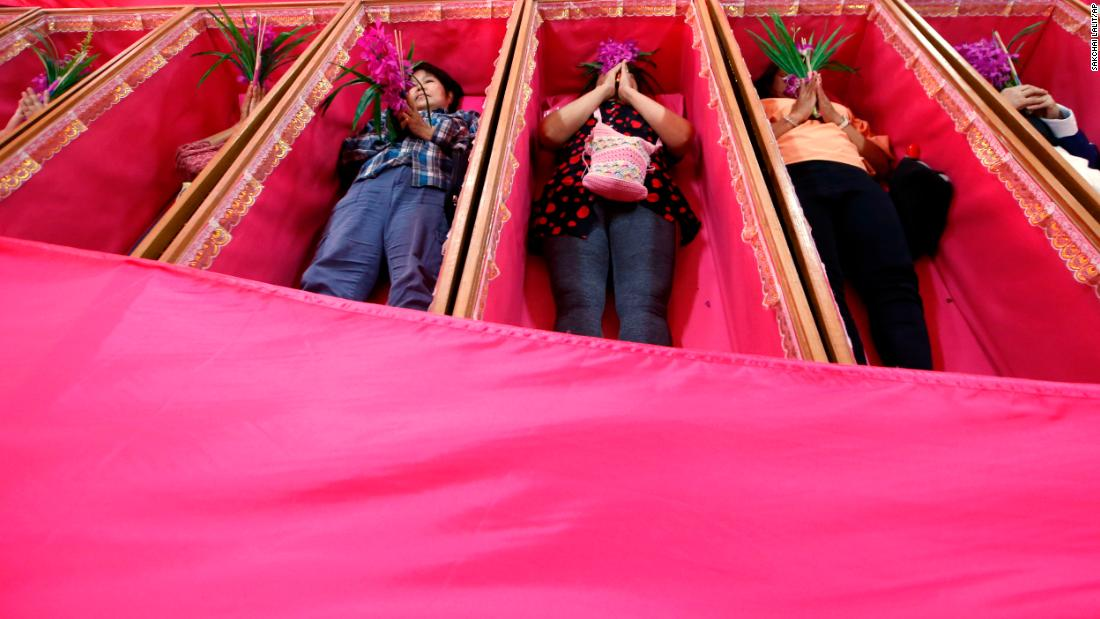 Worshippers pray as they take turns lying in coffins at the Takien temple in Bangkok, Thailand, on Monday, December 31. The coffin ceremony symbolizes death and rebirth, and worshippers view it as a fresh start for the new year.