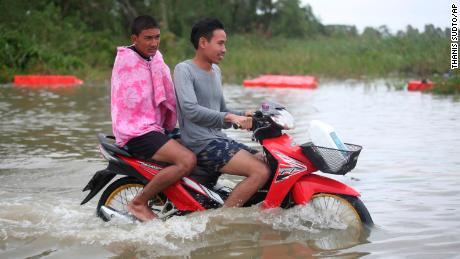 Thai men ride a motorcycle Friday through floodwaters from Tropical Storm Pabuk in the Pak Panang district of Nakhon Si Thammarat province.