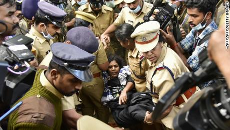 Indian police protect a female Hindu devotee after her entry to Sabarimala temple was blocked by hardline activists, December 24, 2018.