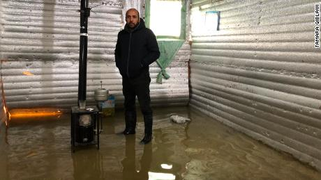 Mohammed Kassaf stands in the living room area of his tarpaulin tent.