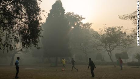 Indian youths play football amid air pollution smog at Lodhi Gardens in New Delhi on January 12, 2019.