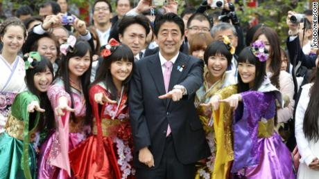 Japanese Prime Minister Shinzo Abe (C front) poses for photos with the five members of girl pop idol group Momoiro Clover Z during the government's cherry blossom viewing garden party in Tokyo on April 20, 2013.