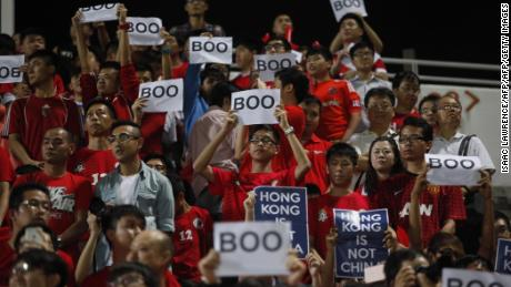 """Hong Kong fans hold up signs that read """"Boo"""" while the national anthem was being played during a world cup qualifier at Mong Kok stadium in Hong Kong on November 17, 2015."""