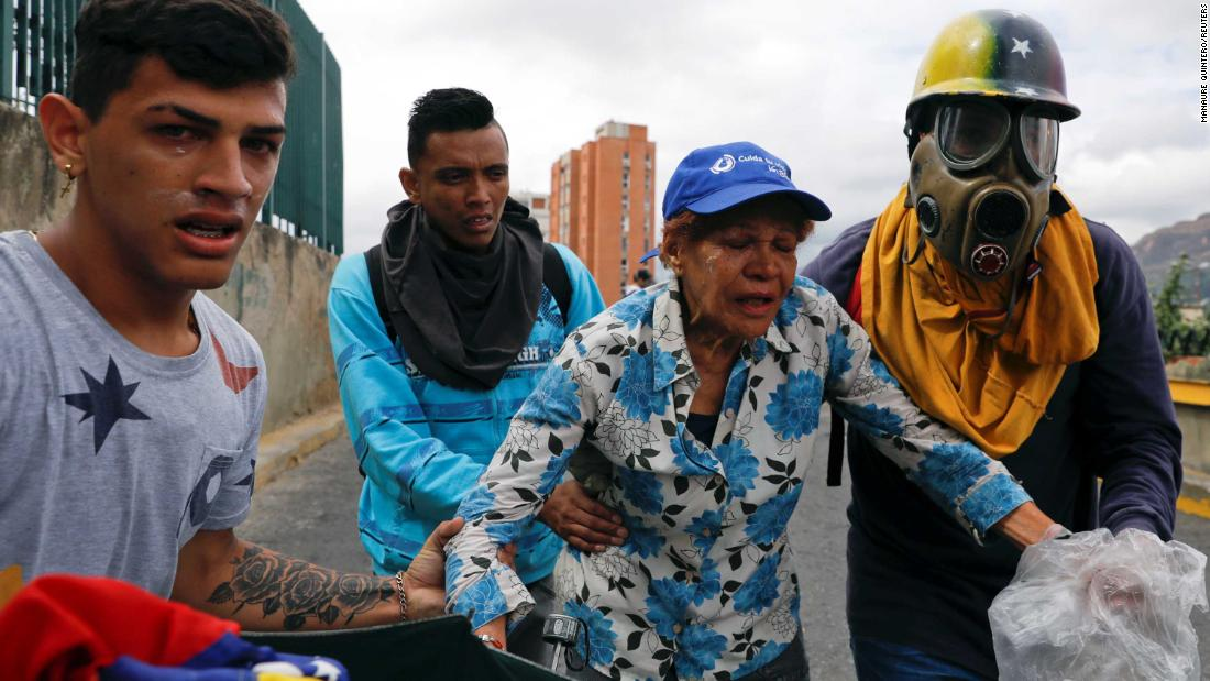 Opposition supporters react to tear gas as they take part in the Caracas rally on January 23. Sporadic clashes erupted, but Maduro's military response to the protests seemed more measured than in the past.