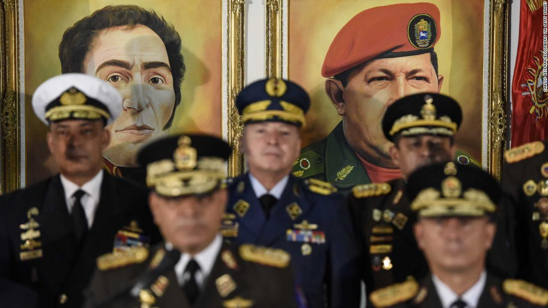Portraits of former Venezuelan leaders Simon Bolivar and Hugo Chavez hover in the background as Venezuelan Defense Minister Vladimir Padrino Lopez, bottom left, addresses a news conference in Caracas on Thursday, January 24. Venezuela's top military officials swore their allegiance to Maduro after other nations recognized Guaido as head of state.