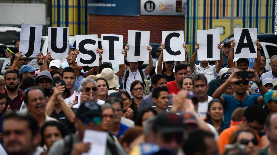 "Supporters of Venezuela's opposition hold up letters that read ""Justice"" at a rally to hear Guaido speak in Caracas on Saturday, January 26."