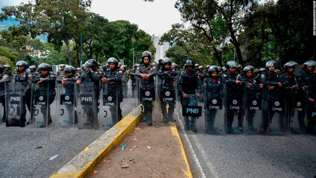 Members of the National Police line up to guard the entrance of Venezuela's Central University in Caracas during an anti-government protest on January 30.