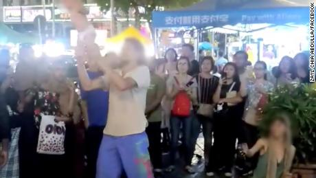 Russian couple swings baby around by ankles in freakish  street performance