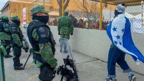 Un hombre envuelto en una bandera nacional hondureña camina junto a un cordón de policía militar frente a un refugio para inmigrantes centroamericanos en Piedras Negras, México, el 10 de febrero. {19459024)<noscript> <img alt=