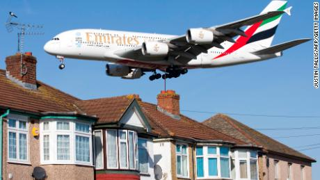 An Emirates Airbus A380 aircraft is seen above roof top as it comes into lane at Heathrow Airport in west London on February 18, 2015. Heathrow's expansion plan to build a third runway is backed by trade unions, airlines and businesses, but opposed by many residents, British media report. London's Heathrow is Europe's busiest in terms of passenger numbers, and the world's busiest for international passenger traffic. AFP PHOTO / JUSTIN TALLIS (Photo by Justin TALLIS / AFP)        (Photo credit should read JUSTIN TALLIS/AFP/Getty Images)