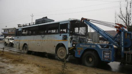 A damaged bus is towed away following the attack.