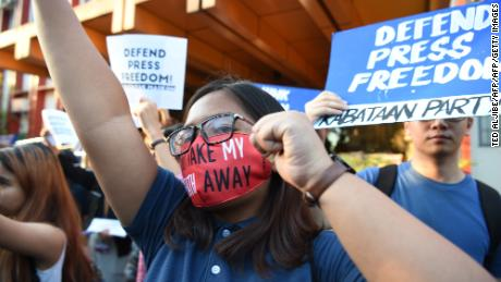 Students hold placards as they shout slogans during a protest at the state university grounds in Manila on February 14, 2019, in support of Ressa.