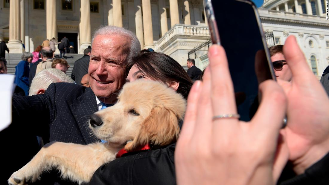 Biden poses for a photo with a dog named Biden as he greets a crowd on Capitol Hill in March 2017.