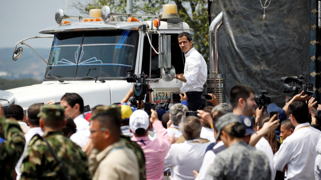 "Venezuelan opposition leader Juan Guaidó stands on a truck carrying humanitarian aid for Venezuela on February 23. ""We have peaceful intentions regarding this humanitarian and multilateral effort,"" Guaido said, speaking at the Colombia-Venezuela border. He described it as a ""peaceful effort that wants to save lives."""