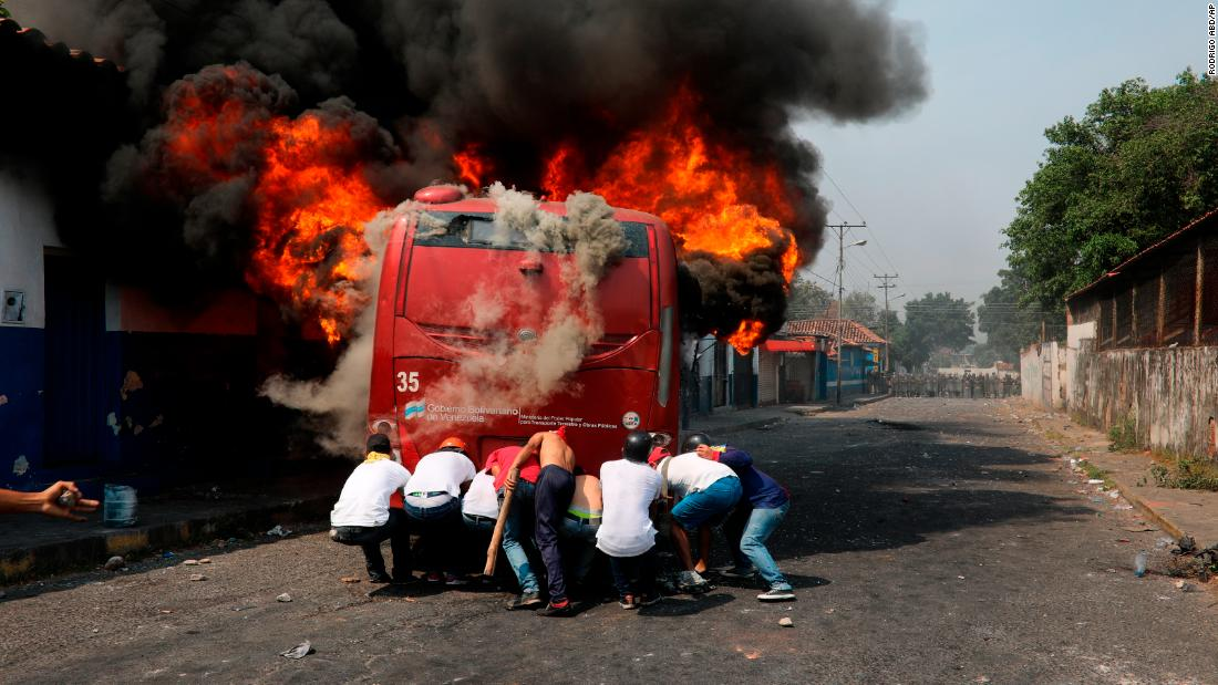 Demonstrators push a bus that was set on fire during clashes with the Venezuelan National Guard in Urena, Venezuela, on February 23.