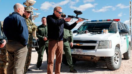 Acting Secretary of Defense Patrick Shanahan, center, fires a modified painted ball gun during a tour of the US-Mexico border at Santa Teresa Station in Sunland Park, N.M., Saturday, Feb. 23, 2019. Standing behind Shanahan is Joint Chiefs Chairman Gen. Joseph Dunford. Top defense officials toured sections of the U.S.-Mexico border Saturday to see how the military could reinforce efforts to block drug smuggling and other illegal activity, as the Pentagon weighs diverting billions of dollars for President Donald Trump's border wall.  (AP Photo/Pablo Martinez Monsivais)