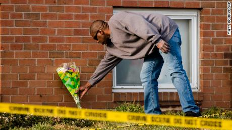 A man places flowers outside the family's apartment on Tuesday.