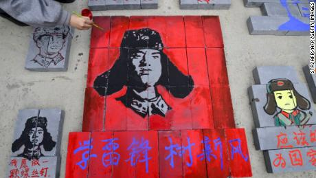 This photo taken on March 12, 2017 shows Chinese students painting portraits of Lei Feng, communist China's most famous model soldier, on bricks at a construction site in Liaocheng, east China's Shandong province.