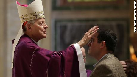Cardinal Donald Wuerl places ashes on the foreheads of Catholics during Ash Wednesday Mass.