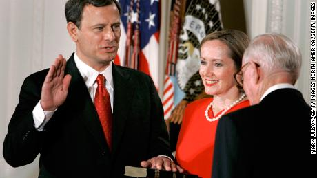 Jane Roberts (C) holds a Bible as John Roberts (L) raises his right hand as he is sworn in as Chief Justice of the United States Supreme Court by Associate Justice John Paul Stevens during a ceremony in the East Room at the White House Sept. 29, 2005, in Washington DC.