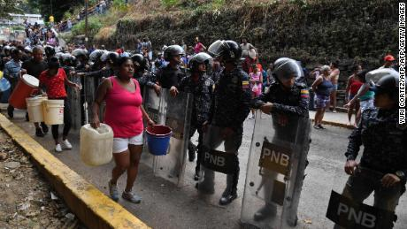 Police help distribute drinking water in Caracas on March 11.