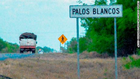 A truck drives past a sign on the Reynosa-San Fernando highway, near the location where 19 migrants went missing.
