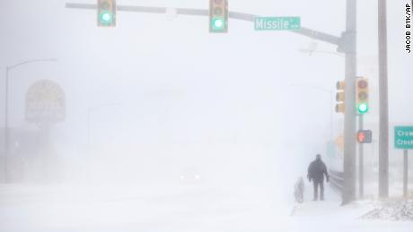 James Little crosses the street during a blizzard on Wednesday, March 13, 2019, in Cheyenne, Wyo.  Heavy snow hit Cheyenne about mid-morning Wednesday and was spreading into Colorado and Nebraska.  (Jacob Byk/The Wyoming Tribune Eagle via AP)