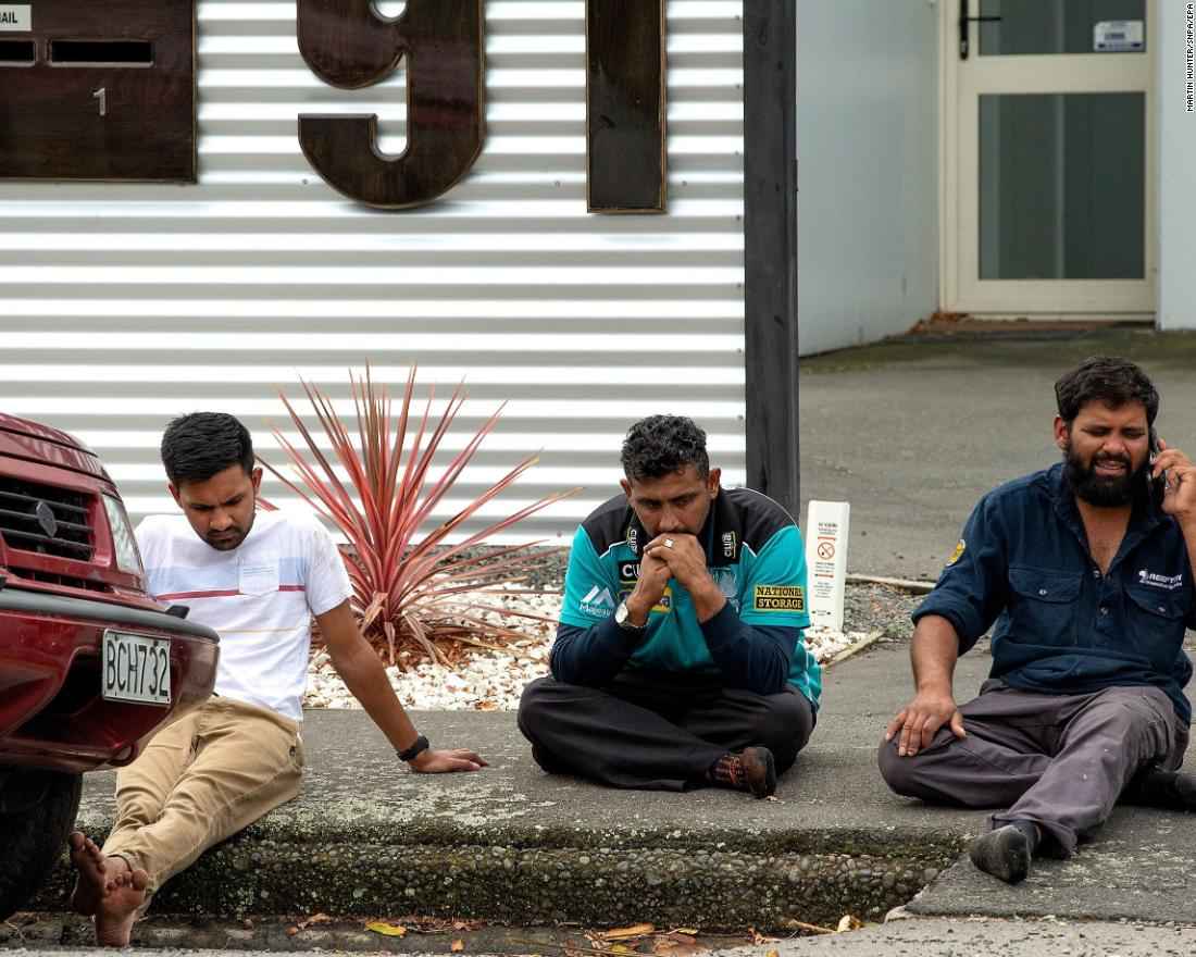 People grieve on a curb in Christchurch.