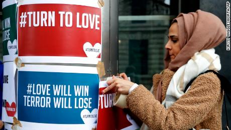 A demonstrator hangs banners from multi-faith group 'Turn to Love' during a vigil at New Zealand House in London.