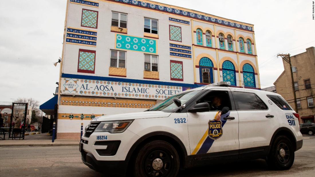 Police officers sit in their vehicle outside the Al Aqsa Islamic Society mosque in Philadelphia on March 15. Many cities bumped up their police presence outside of mosques.